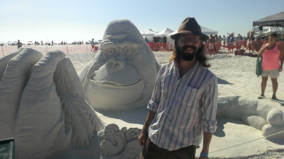 "SRQ Magazine Phil Lederer poses with ""Siesta Selfie"" sand sculpture in the 2014 Crystal Classic competition."