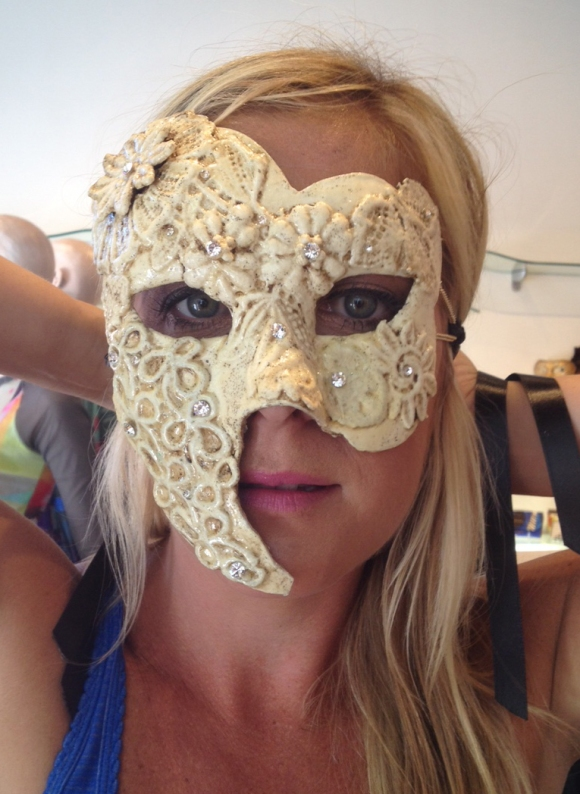 SRQ Client Development Director Ashley Ryan tries on a feminine Phantom of the Opera style mask at i tesori. Photo credit: Mary Darby Guidroz